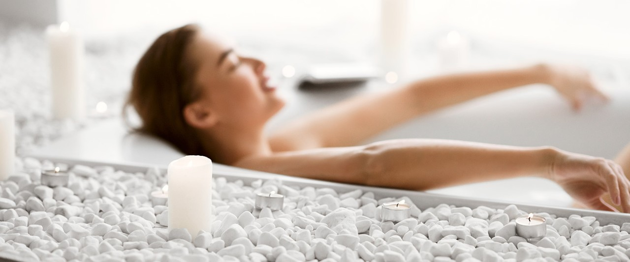 Enjoy Spa Procedure. Woman Lying In Bath With Foam And Candles
